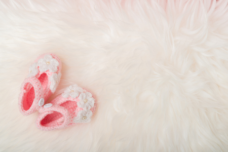 Close up Baby girl knitted shoes on white blanket background.Happy new year greeting card with copy-space. New born celebration holiday concept. Stockfoto