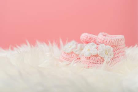 Close up Baby girl knitted shoes on white blanket background.Happy new year greeting card with copy-space. New born celebration holiday concept. Stock Photo