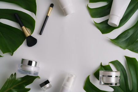 White cosmetic products and green leaves on white background. Natural beauty blank label for branding mock-up concept. Archivio Fotografico