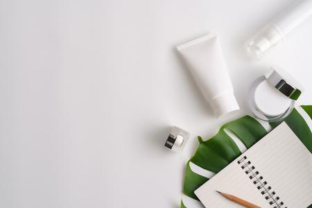 Produtos cosméticos brancos e folhas verdes sobre fundo branco. Produtos de beleza natural para marcar o conceito de mock-up.
