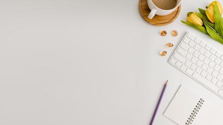 Tavolo da ufficio bianco con taccuino vuoto, computer, forniture e tazza di caffè. Vista dall'alto con spazio di copia. Disteso. Archivio Fotografico