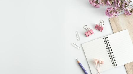 In stile stock photography tavolo scrivania bianco con taccuino vuoto, tastiera, amaretto, forniture e tazza di caffè. Vista dall'alto con spazio di copia. Disteso.