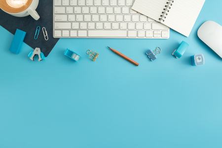 Flat lay, top view office table desk. Work space with blank note book, keyboard, blue office supplies and coffee cup on white background.