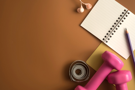 Styled stock photography of fitness equipment dumbbells notepad pencil and earphone on brown background. Flat lay.
