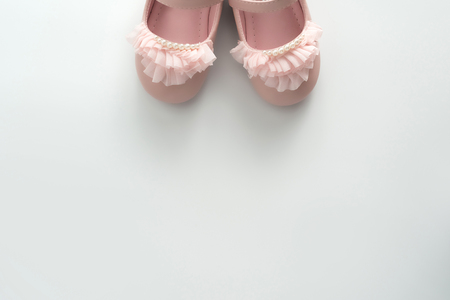 Cute pink baby girl shoes close up on white background Foto de archivo