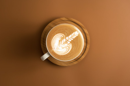 Coffee cup with wooden plate on brown color background.