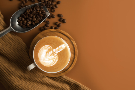 Coffee cup with wooden plate, roasted coffee beans on brown color background.