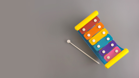 Flat lay composition with brilliant basics xylophone baby toy on color background.Top view, copy space