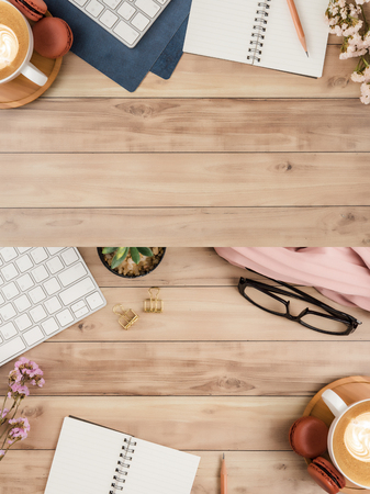 Flat lay, top view office table desk. Workspace with blank note book, keyboard, macaroon, office supplies, flowers, green leaf, gold ornament and coffee cup on wooden background.