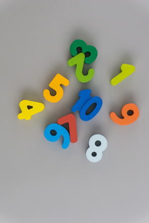 Flat lay composition with numbers wooden baby toy on color background.Top view, copy space