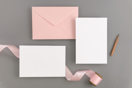 A wedding mock up concept. Wedding Invitation, envelopes, cards Papers on color background with ribbon and decoration. Top view, flat lay, copy space