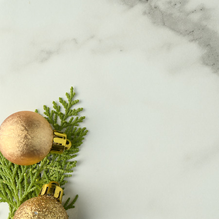 Christmas background template with frame of fir branches and christmas ornament in white marble texture background. Flat lay, top view Foto de archivo - 121399579