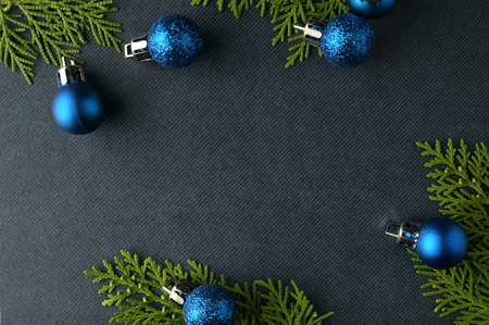Christmas background template with frame of fir branches and christmas ornament in blue texture background. Flat lay, top view