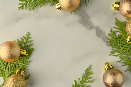 Christmas background template with frame of fir branches and christmas ornament in white marble texture background. Flat lay, top view Foto de archivo - 121399607