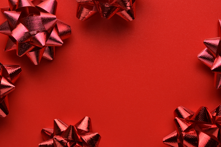 Flat lay, Top view minimal composition background of red decorative Christmas gift bows. New Year and Christmas concept with copyspace.