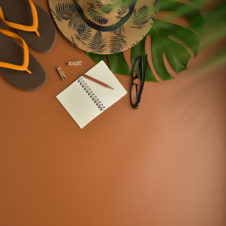 Flat lay, top view workspace with eye glasses, notebook, hat, pencil, green leaf, shoes and coffee cup on brown background. Summer stylish traveller blogger concept.