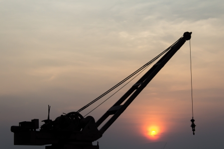lifting jack: Hooke on cranes silhouettes over sun at sunrise  Stock Photo