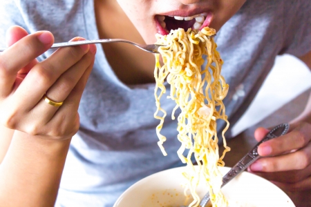 eating noodles: woman eating instant noodles  close up Stock Photo