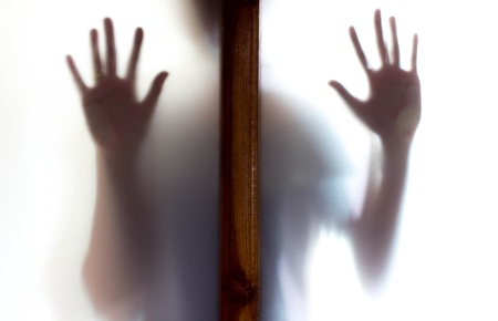 malice: Shadow of woman standing behind door frosted glass