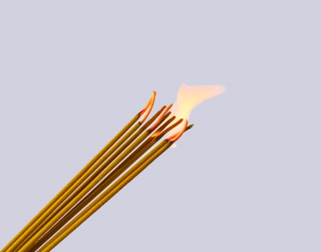 Photo of a burning incense stick with smoke on a grey background photo