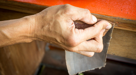 sandpaper: Hands of a man with sandpaper doing  work is  wooden table