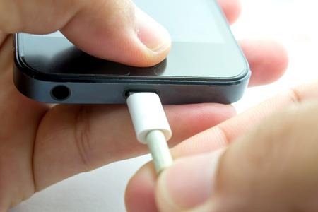 telefonos movil: Mano con carga de tel�fono m�vil en el fondo blanco.