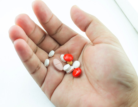 Pills in hand on white background photo