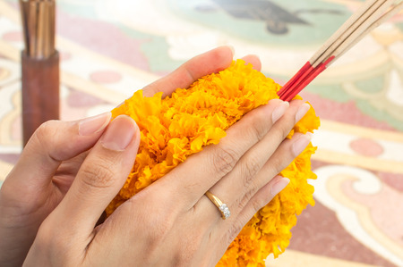 detail of asian woman praying buddha with Floral garland - Marigold and incense stick photo
