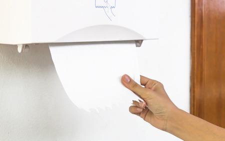 Frau Hand ziehen Gewebe Papierhandtuchspender an der Wand im Badezimmer