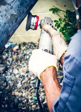 polisher: Man using hold electric polisher on pole steel