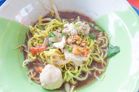 thai pork noodle thicken soup in bowl