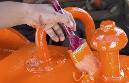 A hand is working with paint brush with orange paint photo