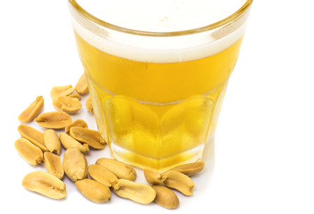 Beer in glass and fried  peanuts on white background photo