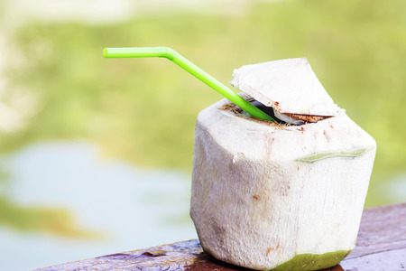 Coconut - Tropical green coconuts opened for the drinking water with straws. photo