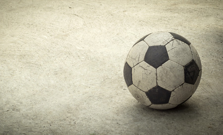 raged: Old football on concrete background, retro style Stock Photo