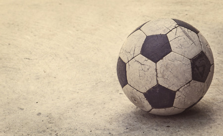 raged: Old football on concrete background, retro style Stock Photo