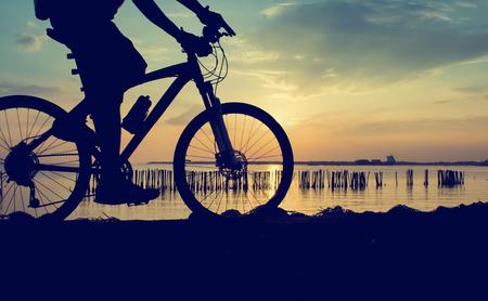 romance: silhouet van de fietser rijden op een racefiets bij zonsondergang