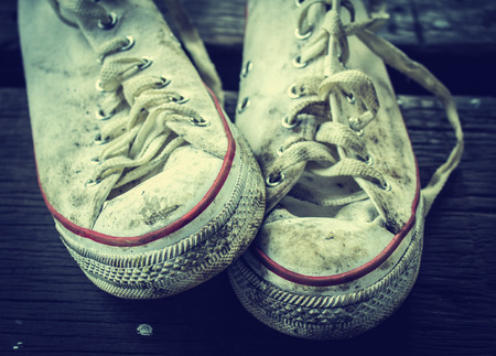 Old sneakers on the wooden floor photo