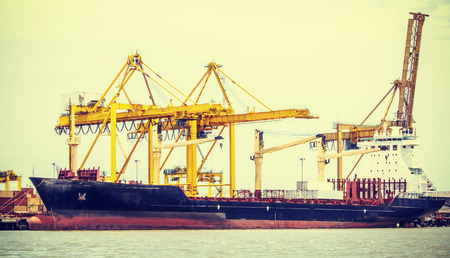 Container Cargo freight ship with working crane loading in shipyard photo