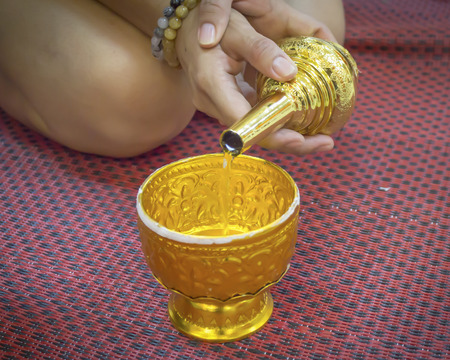 grail: Buddhists grail pouring water  sit on mat