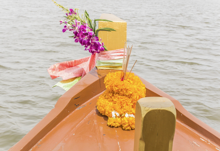 Prow of Thai boat almost tied with three colored clothes and garlands are used to worship the sacred in Thailand believe is prosperity