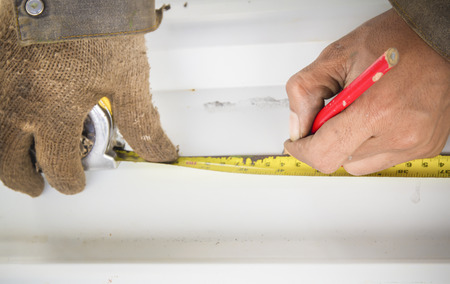 Worker marking plank using pencil and old measuring Imagens