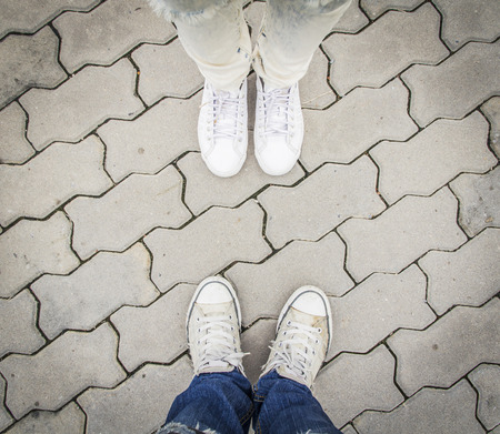 pairs: Two pairs of  sneakers on the background pavement. Hipster style Stock Photo