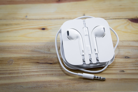 earphone: White earphone on wooden background Stock Photo
