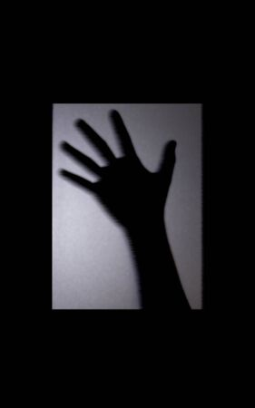 Shadow blur of two hand behind the mirror door.  Halloween concept is background in black and white tone picture style in light turned down low