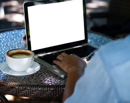 Back view of male person sitting front open laptop computer.In your hand holding a cup of coffee