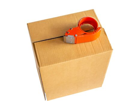 Brown cardboard box and red adhesive tape roll dispenser on white background