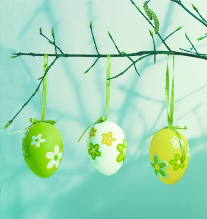 Young branches   with  Easter  eggs.  Arrangement on a blue background. Stock Photo - 6597026