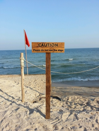 Caution sign beside the beach Stock Photo