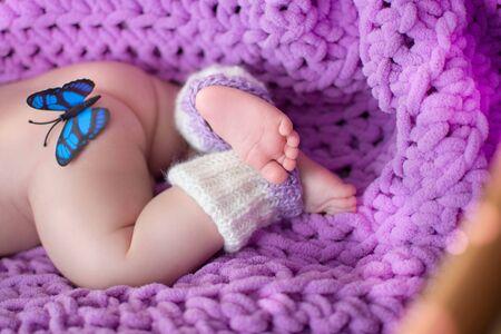 Legs and butt of a newborn on a purple rug Zdjęcie Seryjne